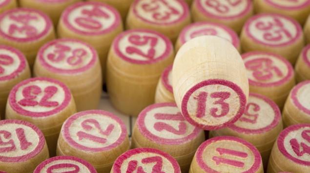 Man sieht ein Bingoscheibe aus Holz mit der Nummer 13, umgeben von weiteren Bingoscheiben.