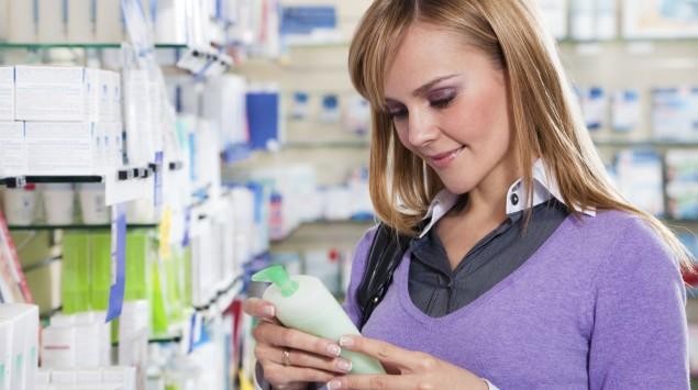 Eine Frau betrachtet ein Pflegeprodukt in einer Drogerie.