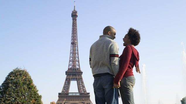 Ein Pärchen steht vorm Eiffelturm in Paris.