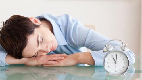 Eine Frau ist am Tisch sitzend eingeschlafen und hat den Kopf auf ihren Armen abgelegt.
