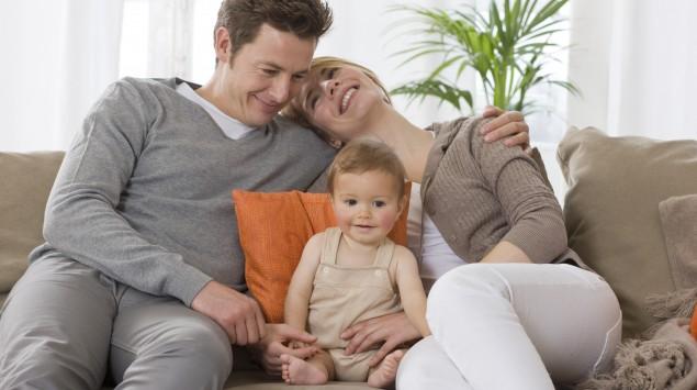 Man sieht ein Elternpaar mit Baby auf einer Couch.