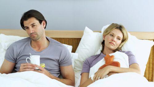 Das Bild zeigt ein erkältetes Pärchen im Bett.