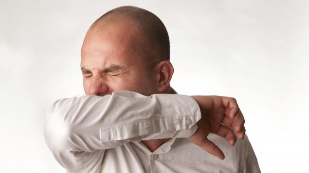 Das Bild zeigt einen Mann, der in seinen Ellenbogen niest.