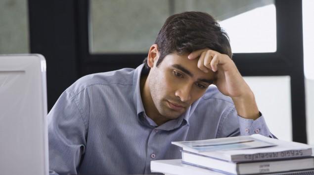 Das Bild zeigt einen Geschäftsmann am Schreibtisch, der sichtlich gestresst wirkt.