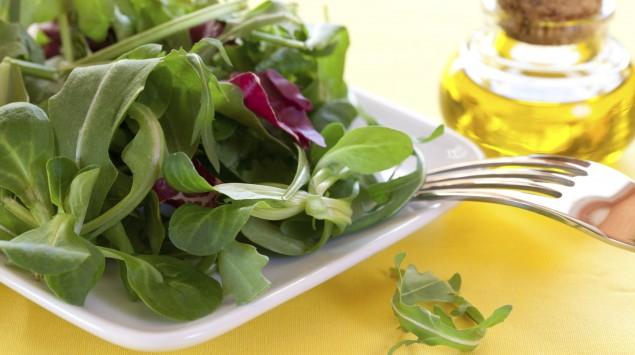 Das Bild zeigt einen grünen Feldsalat mit einer Flasche Öl im Hintergrund.