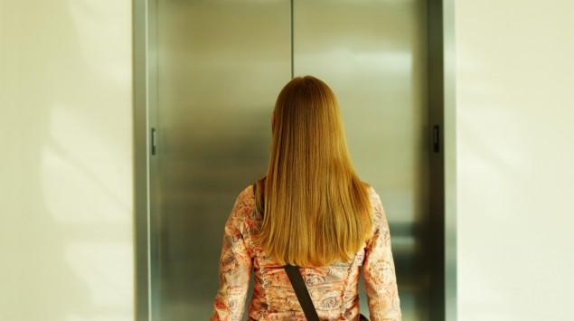 Eine Frau wartet auf den Fahrstuhl.