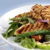 Man sieht einem Teller mit gebratenem Gemüse und Hähnchenbrustfilet.