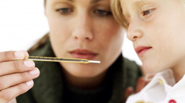 Eine Mutter betrachtet zusammen mit ihrem Kind ein Fieberthermometer.