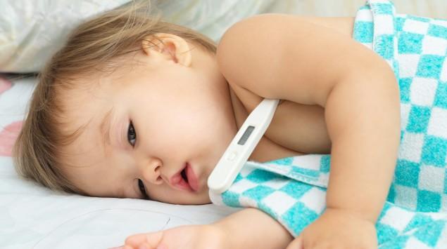 Ein krankes Baby mit Fieberthermometer unterm Arm.