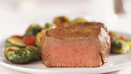 Das Bild zeigt ein angeschnittenes Steak auf einem Teller mit verschiedenen Beilagen.