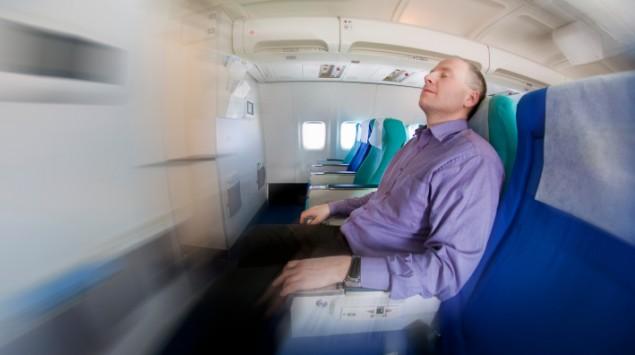 Das Bild zeigt einen Mann, der im Flugzeug schläft.