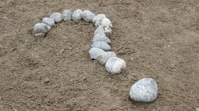 Das Bild zeigt eine Fragezeichen am Strand, das aus weißen Steinen gelegt wurde.