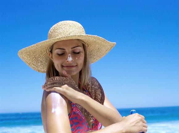Eine Frau am Strand cremt sich ein.