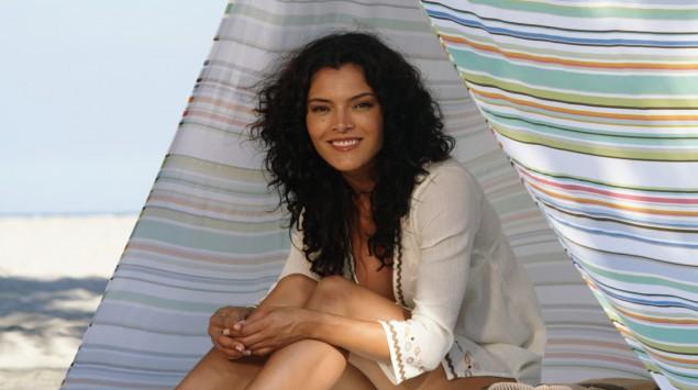 Eine Frau sitzt unter einem Zelt am Strand.