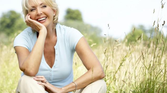 Eine ältere Frau sitzt auf einer Wiese.