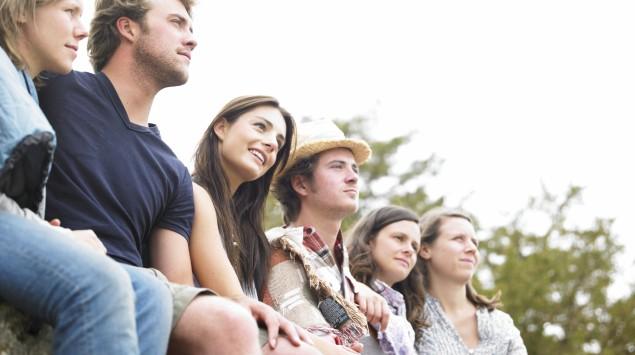 Eine Gruppe von Freunden sitzt auf einer Mauer.