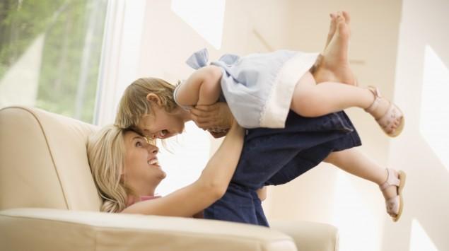 Eine Mutter sitzt auf dem Sofa und hält ihr lachendes Kind in die Höhe.