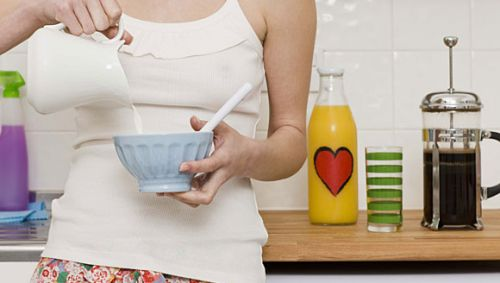 Eine Frau gießt Milch in eine Müslischale.