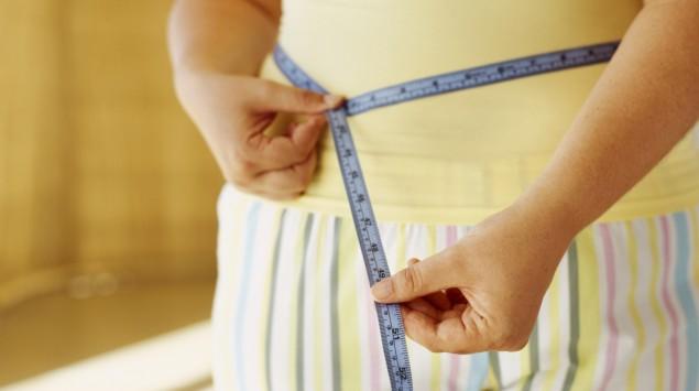 Das Bild zeigt eine übergewichtige Frau, die ihren Bauchumfang misst.