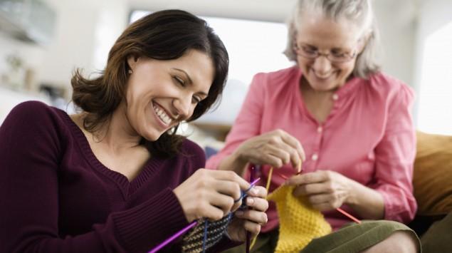 Das Bild zeigt zwei Frauen, die auf einem Sofa sitzen und stricken.