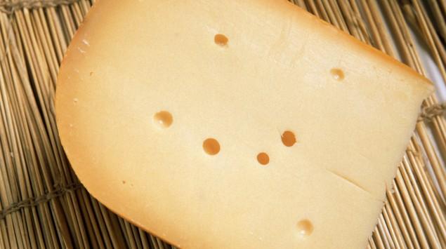 Mna sieht ein Stück Gouda-Käse.