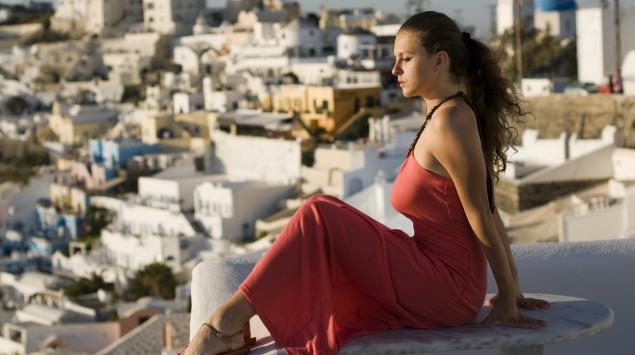 Eine Frau sitzt mit angewinkelten Beinen, im Hintergrund sieht man eine griechische Stadt.
