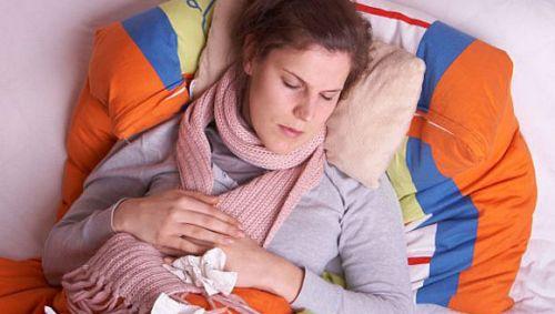 Junge Frau liegt krank im Bett.