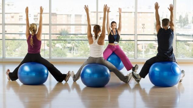 Mehrere Menschen machen Gymnastik mit Bällen.