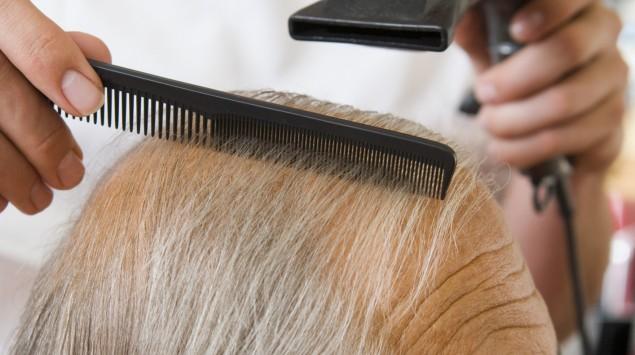 Mann mit ein paar langen Strähnen über der Glatze beim Friseur