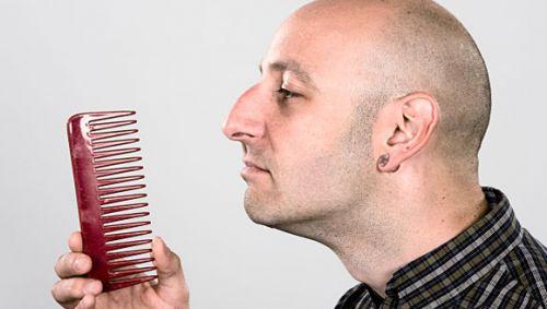 Mann mit Glatze betrachtet einen Kamm.