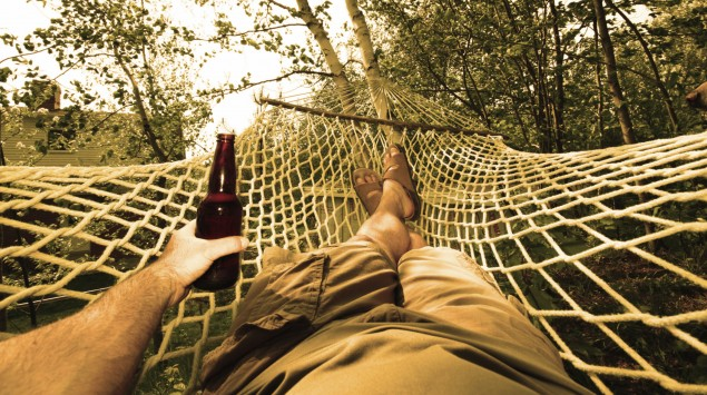 Jemand liegt in einer Hängematte mit einer Flasche Bier in der Hand.