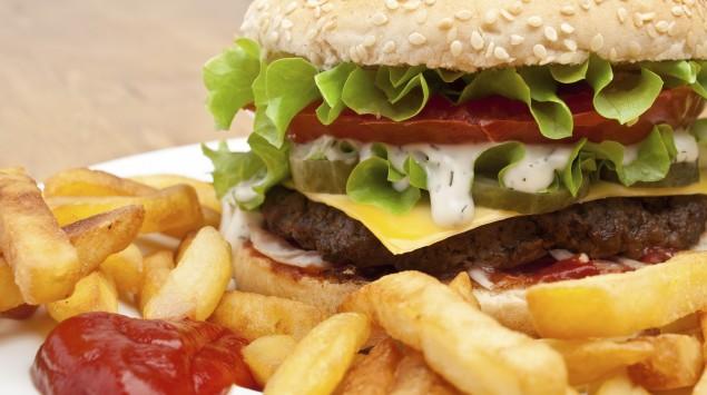 Man sieht einen Teller mit Hamburger, Pommes frites und Ketchup.