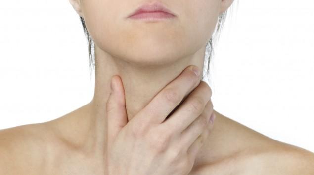 Das Bild zeigt eine Frau, die sich mit den Händen um den Hals fasst.