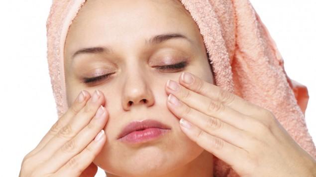 Das Bild zeigt eine Frau mit einem Handtuch auf dem Kopf, die sich das Gesicht eincremt.