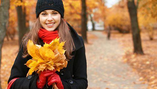 Eine junge Frau hält einen Strauß Herbstblätter in den Händen.