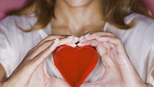 Das Bild zeigt eine junge Frau, die ein großes rotes Herz in den Händen hält.