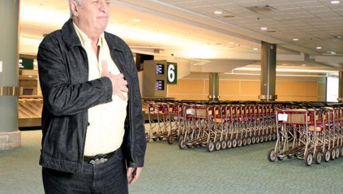 Ein älterer Mann am Flughafen hält sich die linke Brust.