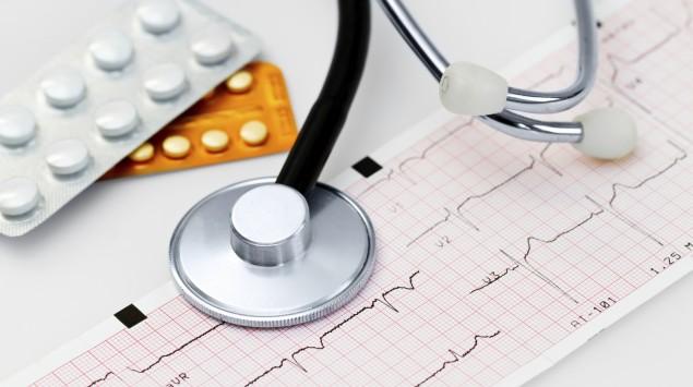 Das Bild zeigt ein, Stethoskop, ein EKG-Streifen und einige Medikamente.