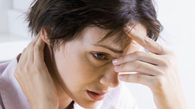 Das Bild zeigt eine nervöse Frau, die ihren Kopf hält.