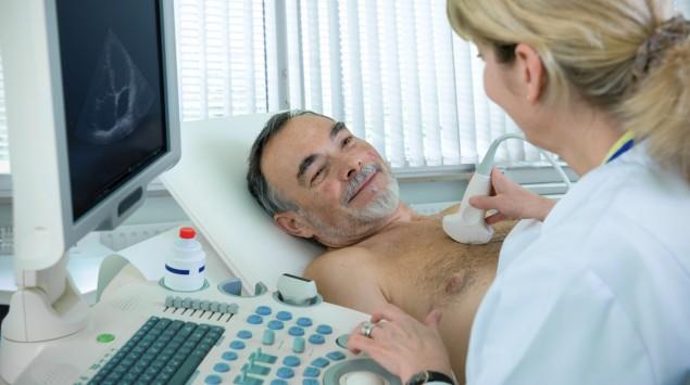 Das Bild zeigt eine Ärztin, die das Herz eines Mannes mittels Ultraschall untersucht.