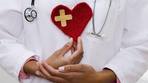 Ein Arzt hält ein rotes Stoffherz vor die Brust.