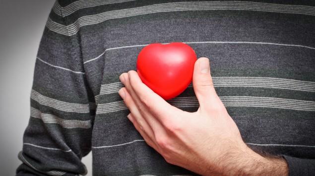 Ein Mann trägt ein rotes Plastikherz an seiner rechten Brust.