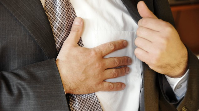 Das Bild zeigt einen Mann, der sich mit seiner Hand an sein Herz fasst.