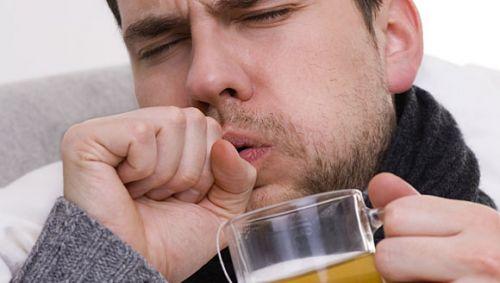 Mann mit Glas Tee in der Hand hustet.