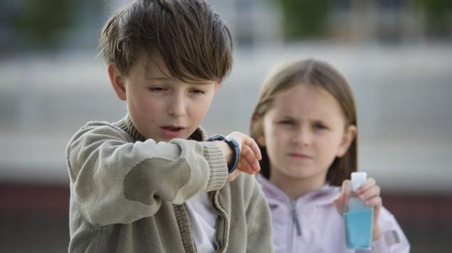 Ein kleiner Junge hustet in den Ärmel; im Hintergrund ein Mädchen.