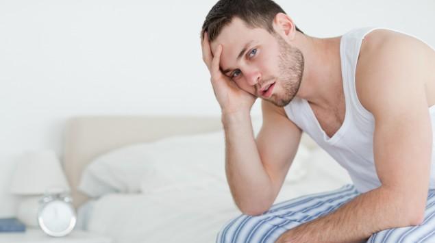 Ein  nachdenklicher Mann sitzt im Nachtanzug auf der Bettkante.