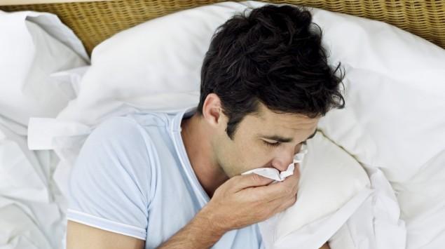 Das Bild zeigt einen Mann, der krank im Bett liegt.