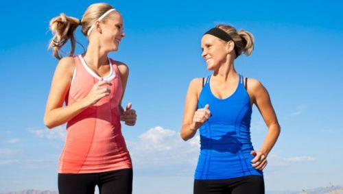 Man sieht zwei Frauen, die joggen und sich unterhalten.