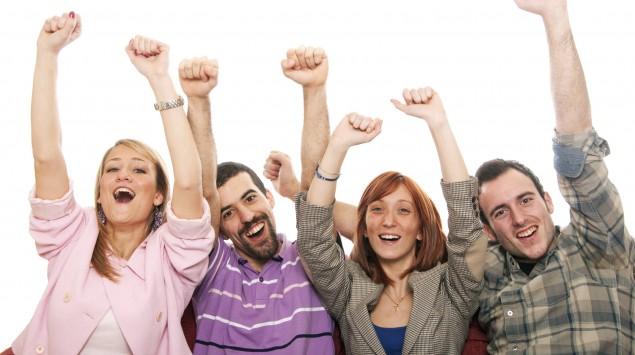 Eine Gruppe junger Leute sitzt auf dem Sofa und reckt jubelnd die Arme in die Luft.