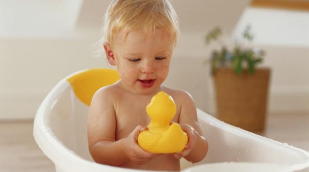 Kleiner Junge sitzt in Kinderbadewanne und spielt mit Quietscheente.